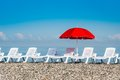 Sun umbrella and beach beds on the shingle beach Royalty Free Stock Photo
