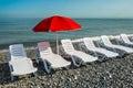 Sun umbrella and beach beds on the shingle beach Royalty Free Stock Photo