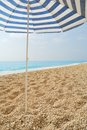 Sun umbrella stuck in a pebble beach with blue sea Royalty Free Stock Photography