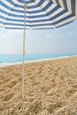 Sun umbrella stuck in a pebble beach with blue sea Royalty Free Stock Photography