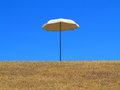 Sun umbrella up on hill the comical scene of a single a an already dried lawn set against a clear blue sky Stock Photos