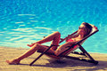 Sunbath woman relax by the pool take sunny summer day Royalty Free Stock Photo