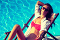 Sunbath woman with sunglasses take by the swimming pool hot summer day Stock Image