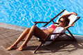 Sunbath young beautiful woman in bikini and sunglasses by the pool take Royalty Free Stock Photo