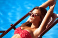 Sunbath young beautiful young woman in bikini and sunglasses by the pool take Royalty Free Stock Photos