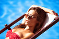 Sunbath young beautiful young woman in bikini and sunglasses by the pool take Royalty Free Stock Photography
