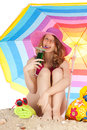 Sunbathing at the beach with colorful parasol woman sitting pink hat under isolated over white background Royalty Free Stock Image