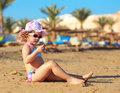 Sunbathing kid girl in hat sitting on sand and looking Royalty Free Stock Photography