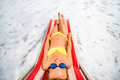 Sunbathing on the red sunbed young and beautiful woman relaxing and having sunbath in sea top view with wide angle Royalty Free Stock Images