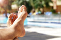 Sunbathing by swimming pool the hotel tourist resort mans legs lying down on a sunlounger looking over the water Stock Images