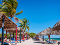 Sunbathing under palm trees and parasols at Playa Ancon in the Caribbean Royalty Free Stock Photo