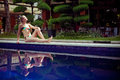 The sunbathing woman near a swimming pool Royalty Free Stock Photography