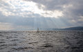Sunbeam on dark sky above the sail boat on st lawrence river Royalty Free Stock Photography