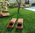 Sunbeds al lado de una piscina en jardín Imágenes de archivo libres de regalías