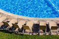 Sunbeds near a swimming pool Royalty Free Stock Photo
