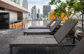 Sunbeds next to a swimming pool on rooftop brown and orange in bangkok thailand Stock Image
