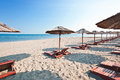 Sunbeds and parasols on the beach Stock Images