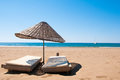 Sunbeds and rattan parasols on sandy seaside beach Stock Photo