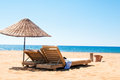 Sunbeds and rattan parasols on sandy seaside relax Royalty Free Stock Photography