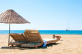 Sunbeds and rattan parasols on sandy seaside summer relax Stock Image