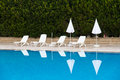 Sunbeds and swimming pool umbrellas near blue clear Royalty Free Stock Photo