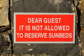 Sunbeds warning a sign to say its not allowed to reserve by guest Royalty Free Stock Photography
