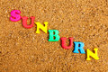 Sunburn the word written in alphabet letters on a sand background Stock Images