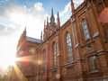 Sunburst on an old red brick catholic church the exterior facade with its arched windows of against a cloudy blue sky in a Stock Photo