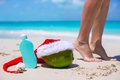 Suncream santa hat on coconut and tanned female legs at white beach Royalty Free Stock Photography