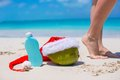 Suncream santa hat on coconut and tanned female legs white beach Royalty Free Stock Photography