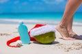 Suncream santa hat on coconut and tanned female legs white beach Stock Images