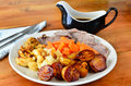 Sunday dinner traditional roast lamb lunch with roast potatoes carrots lamb and gravy boat on the side Royalty Free Stock Photos
