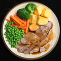 Sunday roast lamb dinner with gravy potatoes broccoli peas carrots and Stock Photo