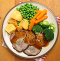 Sunday roast pork dinner with vegetables and gravy Royalty Free Stock Images