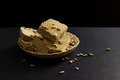 Sunflower halva with seeds on plate, on black background Royalty Free Stock Photo