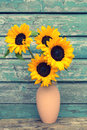 Sunflowers in the vase against old wooden wall Royalty Free Stock Photo