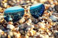 Sunglasses on the beach with sea reflection in them Royalty Free Stock Photo