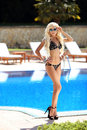 Sunglasses. Beautiful fashion blond slim woman in black bikini p Royalty Free Stock Photo