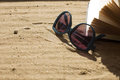 Sunglasses and book on sand Royalty Free Stock Photo