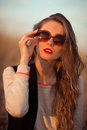 Striking,stunning,dazzling,staggering,exquisite,attractive,beautiful girl held modern sunglasses.Creative sunglasses on her face. Royalty Free Stock Photo