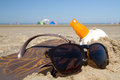 Sunglasses and suntan oil slippers on the beach Stock Photos