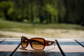 Sunglasses on the table in the sun on a wooden table Royalty Free Stock Photo