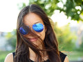 Sunglasses woman funky portrait outdoor with hair flying young girl wearing colored outside looking at camera smiling Stock Photos