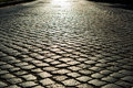 Sunlight on cobblestone road. old stone texture Royalty Free Stock Photo