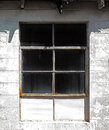 Sunlit industrial window a metal framed mounted in a breeze block building wall Royalty Free Stock Photography