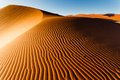 Sunlit namibian desert dunes sand ripple pattern rises to ridge top this is the oldest in the world completely devoid of Royalty Free Stock Photos