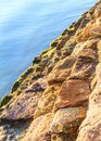Sunlit rock sea wall a seal lit up by the dawn sunlight with a calm blue ocean below Royalty Free Stock Image