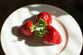 Sunlit strawberries on a white plate Royalty Free Stock Images