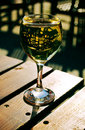 Sunlit white wine glass on a wooden table Royalty Free Stock Photo