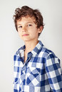 Sunny boy good looking young teenager wearing a blue and white checked shirt looking straight into the camera Royalty Free Stock Photos